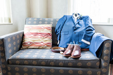Men's Leather New Brown Shoes Closeup Still Life Arrange On Blue Couch With Socks, Watch, Suit For Getting Ready Wedding Preparation In Room