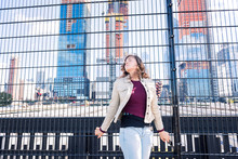 Young Hipster Millennial Woman Looking At Hudson Yards In NYC New York City Manhattan Downtown On High Line Park And Trains Behind Fence, Tourist Looking Up