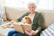 Portrait of happy senior woman enjoying leisure time at home sitting on comfortable couch with pet dog in her lap and reading books