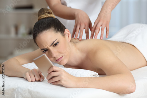 Photo  Angry woman receiving a message during massage