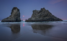 Sea Stacks Reflected In The Water At Sunset On A Beach In Bandon, Oregon