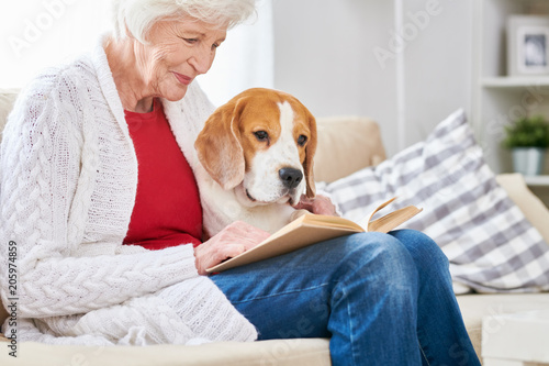 Fotografía  Side view portrait of smiling senior woman sitting on couch with her dog and rea