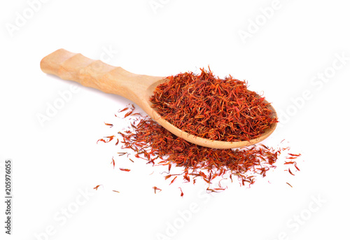dried safflower in wooden spoon and on white background