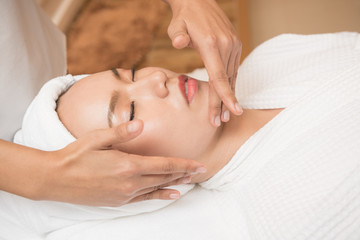 Fototapeta na wymiar Face massage. Spa skin and body care. Close-up of young woman getting spa massage treatment at beauty spa salon. Facial beauty treatment.