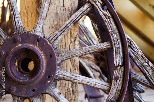Fotografía  Old wooden wagon wheel; antique wagon wheel resting against a post