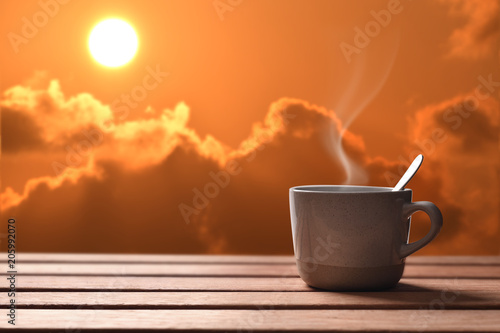 Morning cup of coffee or tea with sunrise background