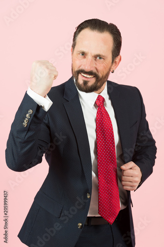 Fotografia, Obraz  Aggressive businessman with beard wearing a blue suit and red tie fighting with angry expression