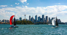Sydney's Iconic Skyline Is Framed Between Two Colorful Sailboats Sailing The City's Beautiful Harbor