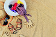 Sand on the beach or in the sandbox and footprints in the sand. Form for sand and children's shoes nearby. Nearby accessories to protect the sun rays of parents. Background image for copy space.