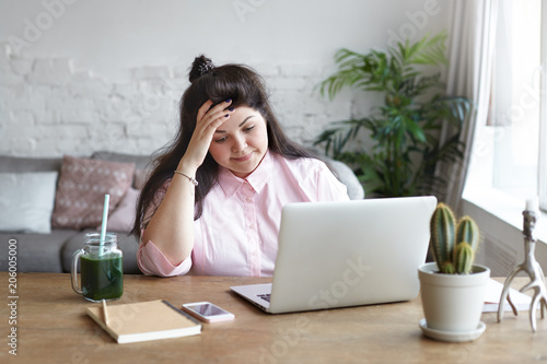 People, job, modern electronic gadgets and technologies. Frustrated young  overweight brunette woman freelancer feeling tired and stressed while  working remotely using laptop pc at home office - Buy this stock photo and