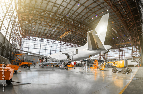 Fototapeta Large passenger aircraft on service in an aviation hangar rear view of the tail, on the auxiliary power unit. Mechanization of the tail is dismantled. obraz