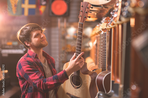 Papiers peints Magasin de musique A young man chooses a guitar