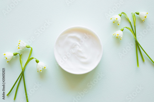 Fototapeta Jar of natural herbal cream for women. Beautiful, fresh snowdrop flowers. Care about clean and soft hands, legs and body skin. Top view. obraz na płótnie