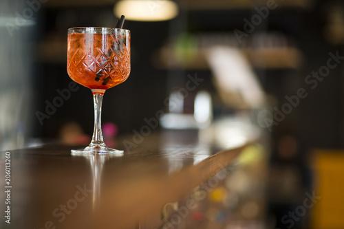Dettaglio di un bicchiere con aperitivo colorato sopra il bancone di un bar