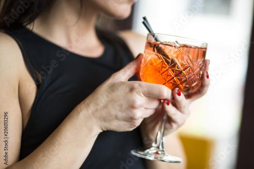 Dettaglio di un bicchiere con aperitivo colorato tenuto da una ragazza in un locale