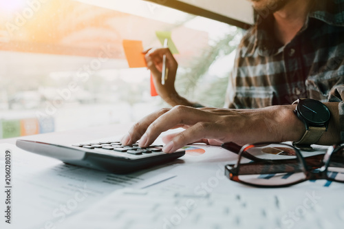 Fotografía  Man calculating individual income tax from financial document during note some d
