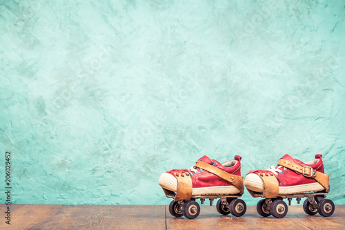 Retro designed classic steel children's roller skates pair with red leather sneakers front mint green concrete wall textured background. Vintage style filtered photo