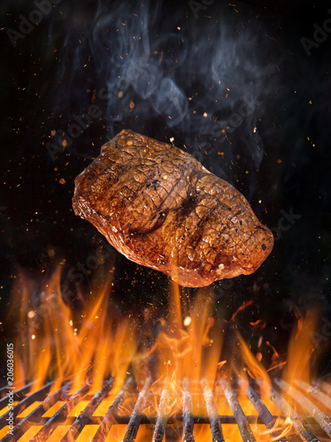 Tasty beef steak flying above cast iron grate with fire flames.