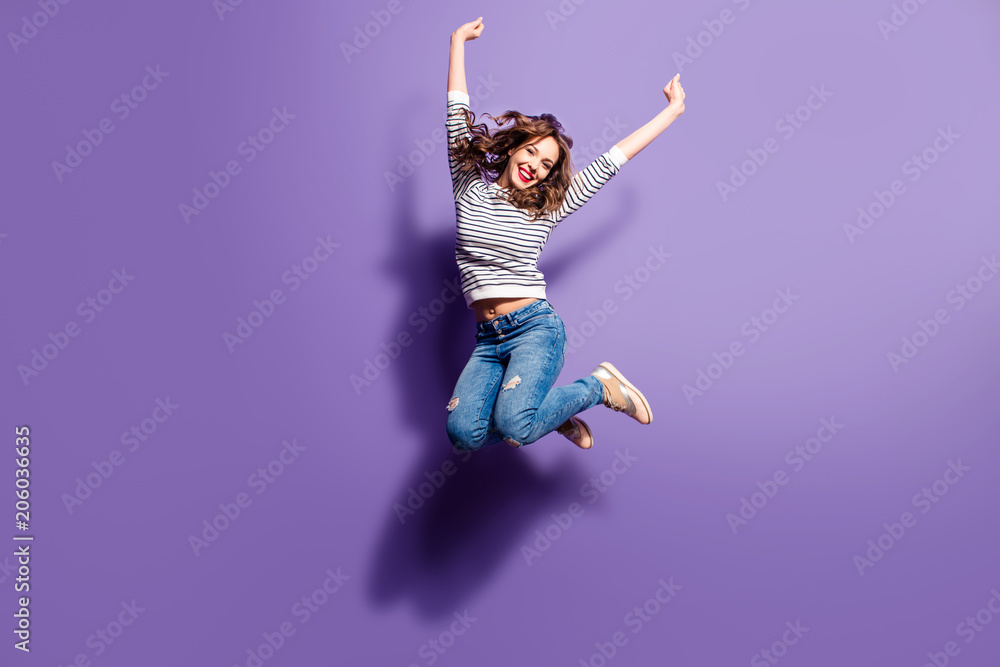 Fototapety, obrazy: Portrait of cheerful positive girl jumping in the air with raised fists looking at camera isolated on violet background. Life people energy concept