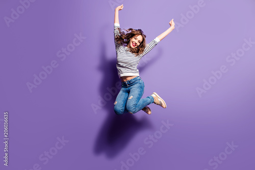 Fotografía  Portrait of cheerful positive girl jumping in the air with raised fists looking at camera isolated on violet background