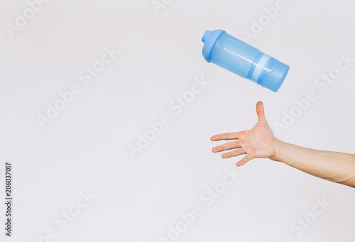 Fotografia  The man catches the shaker a hand. Іsolated white background