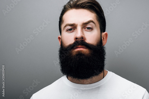 Fotografija Cropped portrait of brutal handsome Caucasian male with trendy beard and mustache, posing on gray studio background