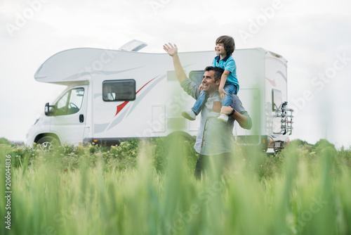 Photo Father and son with the holiday caravan