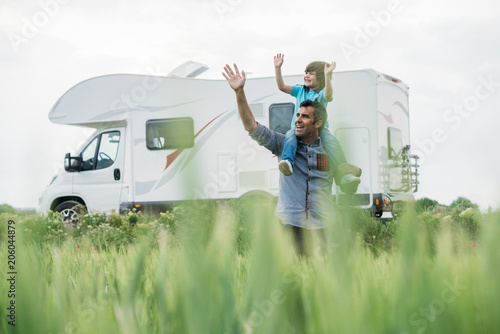 Foto Father and son with the holiday caravan