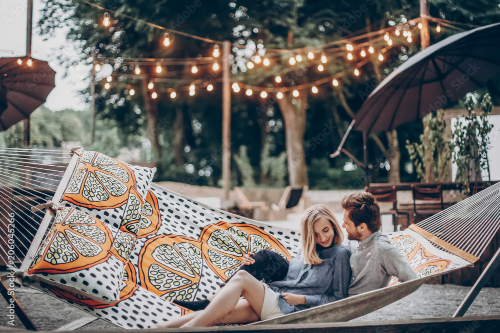 Fototapeta stylish hipster couple cuddling and relaxing in hammock under retro lights in evening summer park. rustic man and woman embracing and resting in forest. space for text. summer vacation