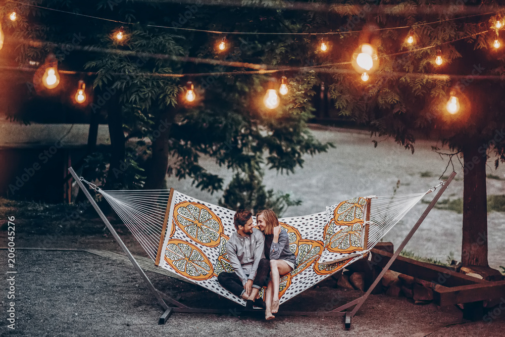 Fototapeta stylish hipster family couple cuddling and relaxing in hammock under retro lights in evening summer park. rustic man and woman embracing and resting in forest. space for text. atmospheric moment