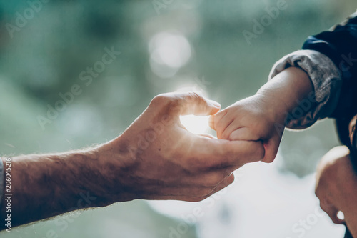 father and little son holding hands in sunlight. father's hand lead his child son in summer forest nature outdoor, trust, protecting, care, parenting family concept. road to life.