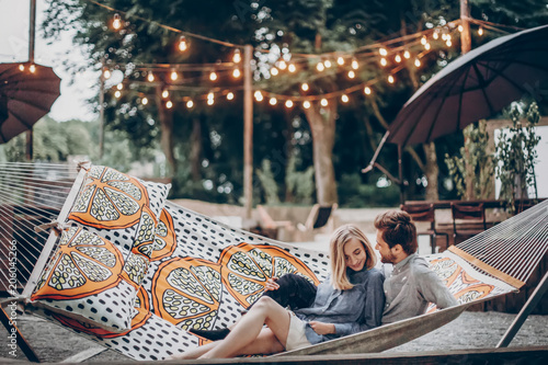 Photo stylish hipster couple cuddling and relaxing in hammock under retro lights in evening summer park