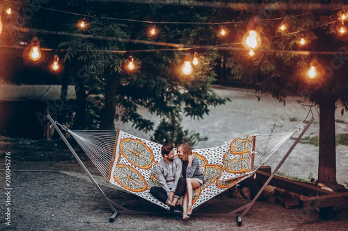 Fototapeta stylish hipster family couple cuddling and relaxing in hammock under retro lights in evening summer park. rustic man and woman embracing and resting in forest. space for text. atmospheric moment obraz
