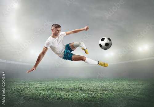 Soccer player on a football field in dynamic action at summer day