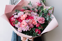 Very Nice Florist Woman Holding A Beautiful Blossoming Flowers Bouquet In Pink Colors Of Ranunculus, Carnations, Roses, Pistachio Leaves On The Grey Wall Background