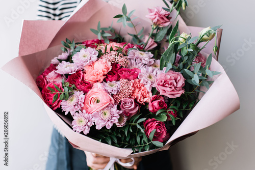 Very nice florist woman holding a beautiful blossoming flowers bouquet in pink colors of ranunculus, carnations, roses, pistachio leaves on the grey wall background © anastasianess