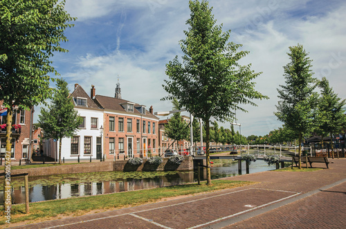 Photo Tree-lined canal with aquatic plants, streets on the banks, brick houses and bascule bridge on a sunny day in Weesp
