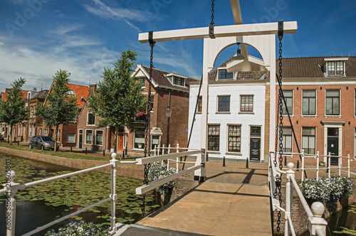 Foto op Canvas Venice Bascule bridge over the canal with aquatic plants, streets on the banks and houses on a sunny day in Weesp. Quiet and pleasant village full of canals and green near Amsterdam. Northern Netherlands.