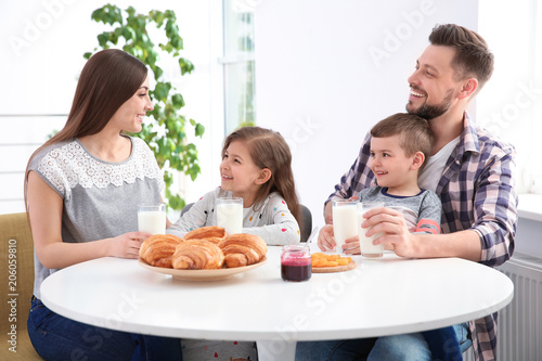 Happy family having breakfast with milk at table