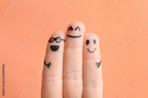 Fotografía  Fingers with drawings of happy faces against color background