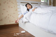 Young Asian woman after eaten pills overdose.Woman's hand lying on the bed with suicide pills.