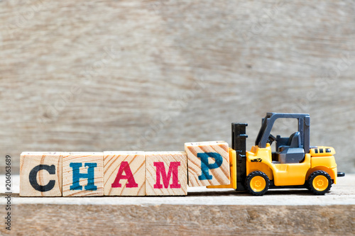 Fotografie, Obraz  Toy forklift hold letter block P to complete word champ on wood background
