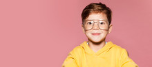 Little Attractive Boy In Yellow Jacket And Big Glasses. Funny Child Posing, Pink Wall On Background. Close Up Portrait Of Smiling Boy.