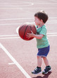 A boy half years playing with a ball on the sports field. Toddler is holding a big basketball ball