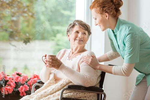 Fotografía A professional caretaker in uniform helping a geriatric female patient on a wheelchair