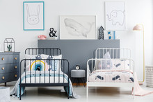 Grey Stool Between Black And White Bed In Children Bedroom Interior With Posters. Real Photo