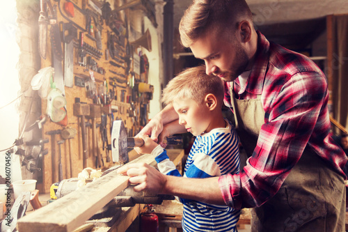 Papiers peints Attraction parc family, carpentry, woodwork and people concept - father and little son with hammer hammering nail into wood plank at workshop