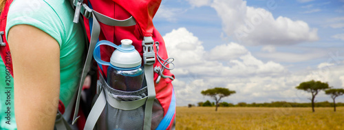 Obraz travel, tourism, hike and people concept - close up of woman with water bottle in backpack pocket over african savannah background - fototapety do salonu