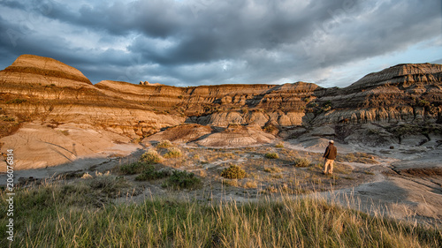 Photo Man standing and taking in the rock formations of the Alberta badlands in Dinosa