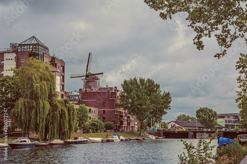 Plakat Duży zalesiony kanał z ceglanymi budynkami, cumować łodziami i chmurnym niebem w Amsterdam. Słynie z ogromnej aktywności kulturalnej, zgrabnych kanałów i mostów. Północnej Holandii. Retro vintage filtr.
